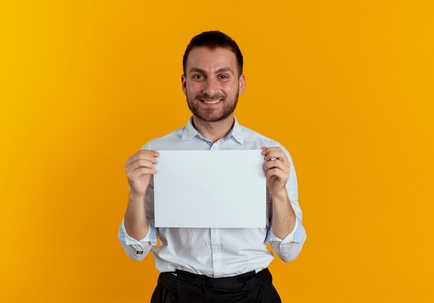 L'uomo bello sorridente tiene il foglio di carta isolato sulla parete arancione