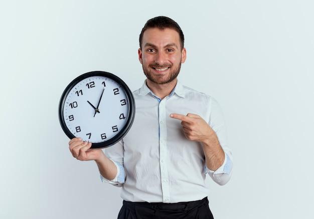 L'uomo bello sorridente tiene e indica l'orologio isolato sulla parete bianca