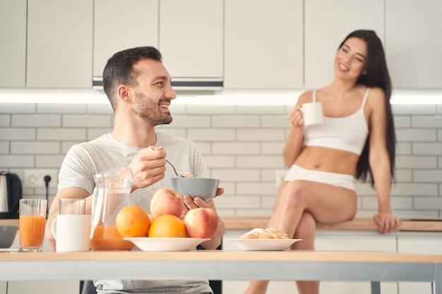 웃고 있는 잘생긴 남자가 아침을 먹고 그의 매력적인 젊은 아내를 바라보고 있다