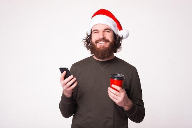 웃는 잘 생긴 남자는 흰색 배경 위에 컵과 그의 전화를 갈 잡고있다.