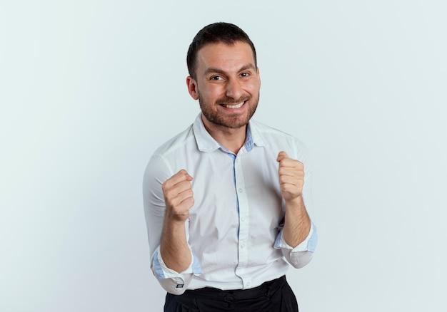웃는 잘 생긴 남자는 흰 벽에 고립 된 주먹을 유지