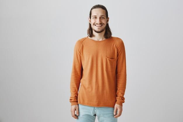 Uomo bello sorridente che sembra felice sopra fondo grigio
