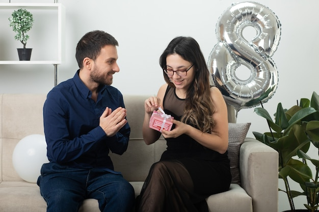 Smiling handsome man looking at pleased pretty young woman in optical glasses opening gift box sitting on couch in living room on march international women's day