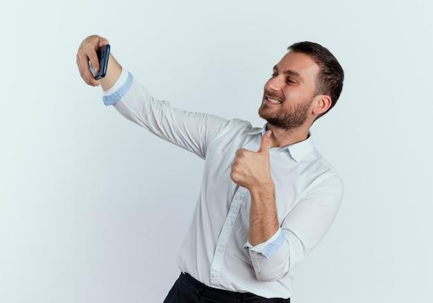 웃는 잘 생긴 남자가 전화를 바라보고 엄지 손가락에 격리 된 흰 벽