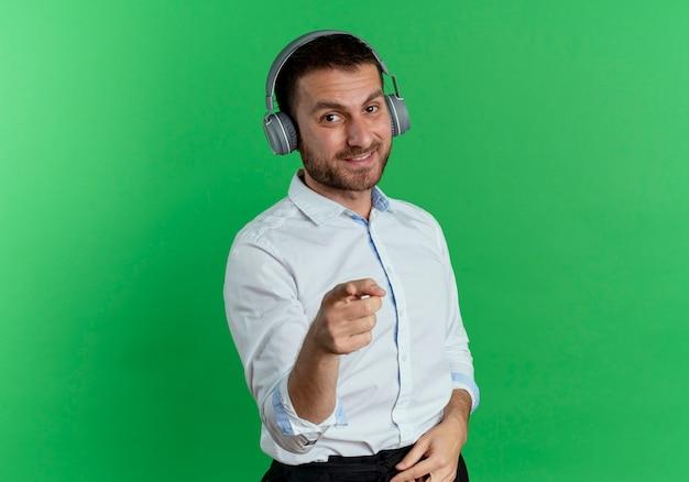 녹색 벽에 고립 된 헤드폰 포인트에 웃는 잘 생긴 남자