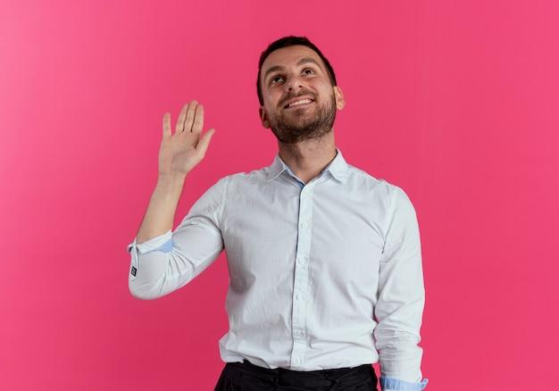 笑顔のハンサムな男はピンクの壁に孤立して見上げる手を上げる