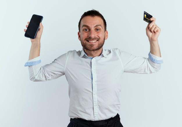 웃는 잘 생긴 남자가 흰 벽에 고립 된 전화와 신용 카드를 들고 손을 올립니다