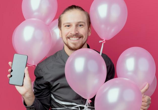 笑顔のハンサムな男は、分離された電話を保持しているヘリウム気球で立っています