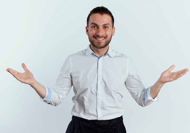 笑顔のハンサムな男は白い壁で隔離の開いた手で立っています