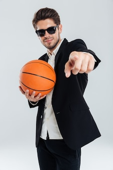 Smiling handsome man in sunglasses and black suit holding basket ball and pointing finger at front over grey wall