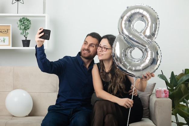 Smiling handsome man taking selfie on phone with pretty young woman in optical glasses holding balloon shaped like eight and sitting on couch in living room on march international women's day