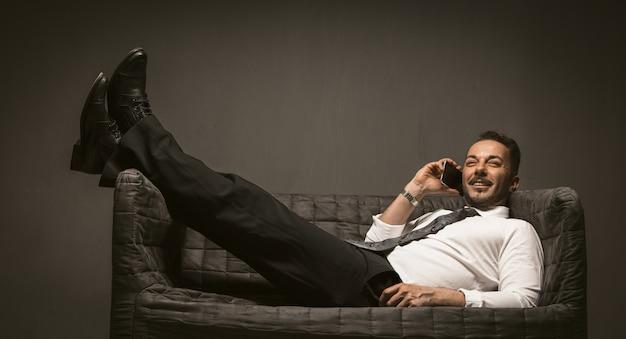ソファーで寝ながらスマートフォンで話しているハンサムな男の笑みを浮かべて、黒のズボンとソファの上の革のブーツに彼の足を投げた