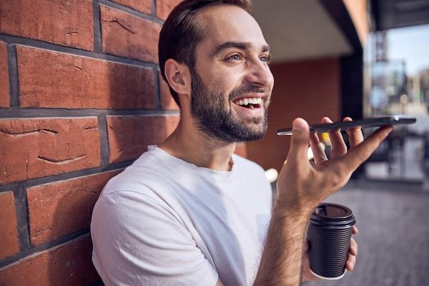 커피와 함께 스마트 폰 얘기 웃는 잘 생긴 남자