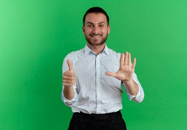 웃는 잘 생긴 남자 엄지 손가락과 녹색 벽에 고립 된 손을 제기