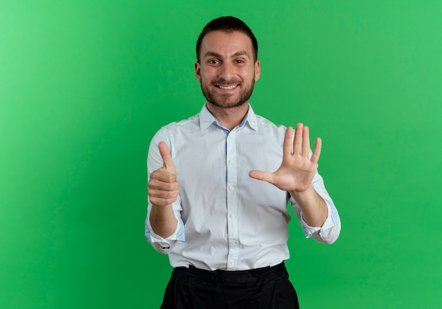 Smiling handsome man thumbs up and raises hand isolated on green wall