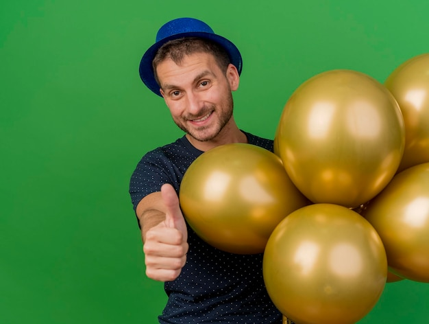 블루 파티 모자를 쓰고 웃는 잘 생긴 남자는 헬륨 풍선을 보유하고 복사 공간이 녹색 벽에 고립 엄지 손가락