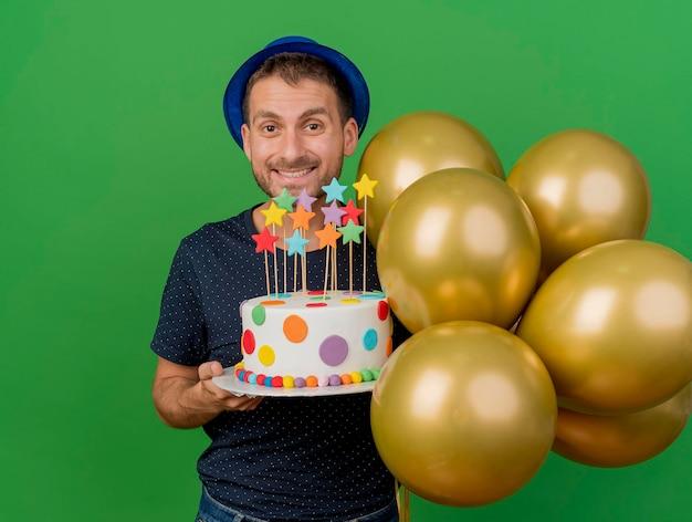 L'uomo bello sorridente che porta il cappello blu del partito tiene i palloni dell'elio e la torta di compleanno isolata sulla parete verde con lo spazio della copia