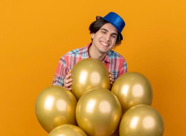 青いパーティーハットを身に着けているハンサムな男の笑顔は、オレンジ色の壁に分離されたヘリウム気球と立っています。