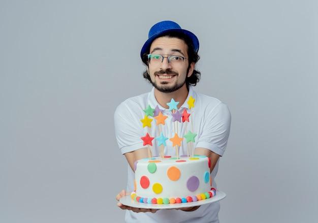 白で隔離のカメラにケーキを差し出す眼鏡と青い帽子を身に着けているハンサムな男の笑顔