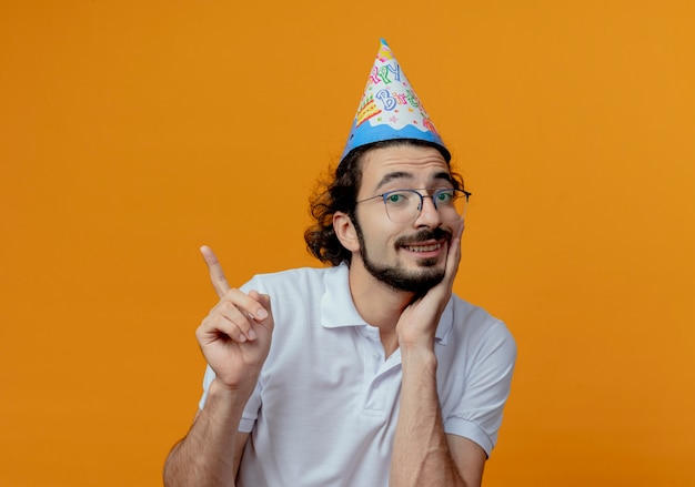 Sorridente uomo bello con gli occhiali e il cappello di compleanno punti a lato mettendo la mano sotto il mento isolato su sfondo arancione con spazio di copia