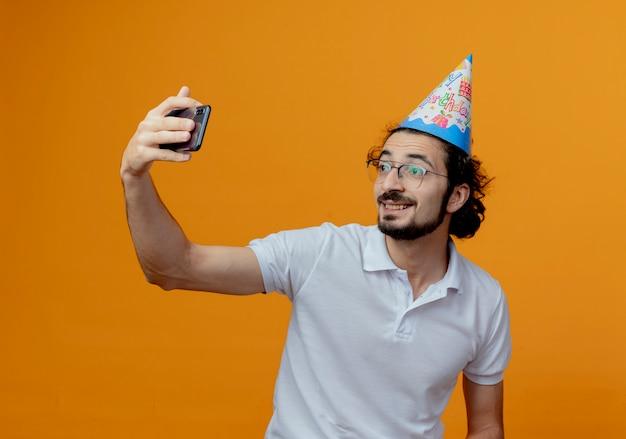 Sorridente bell'uomo con gli occhiali e cappello di compleanno prendere un selfie isolato su sfondo arancione