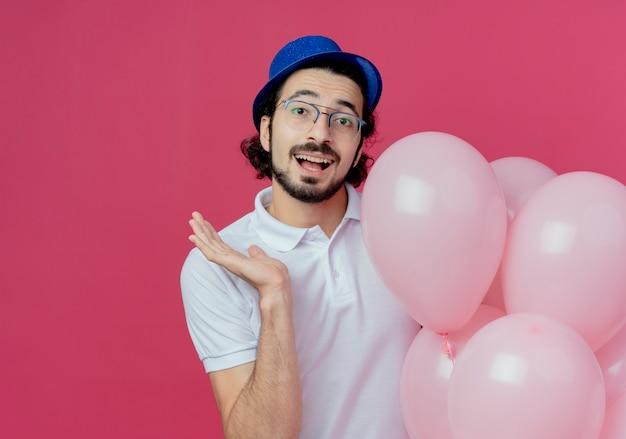 Uomo bello sorridente con gli occhiali e cappello blu che tiene palloncini e punti con mano a lato isolato su sfondo rosa con spazio di copia
