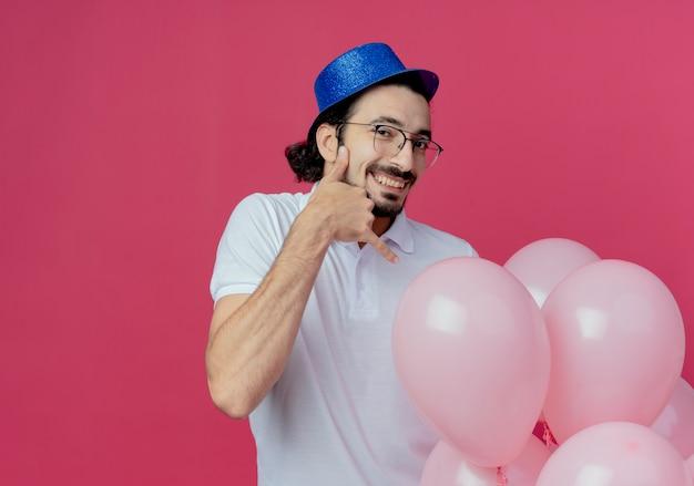 Uomo bello sorridente con gli occhiali e cappello blu che tiene palloncini e che mostra il gesto di chiamata telefonica isolato su sfondo rosa
