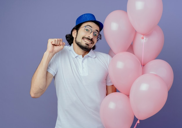 Smiling handsome man wearing glasses and blue hat holding balloons and showing yes gesture isolated on purple