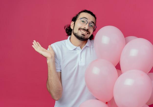 コピースペースとピンクの背景で隔離の風船とポイントを手で横に持って眼鏡をかけてハンサムな男の笑顔