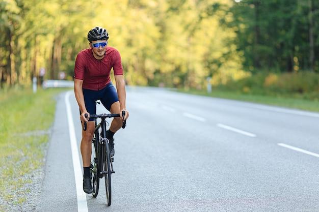 도로 자전거를 타는 동안 보호용 헬멧과 미러 안경을 쓰고 웃는 잘 생긴 남자