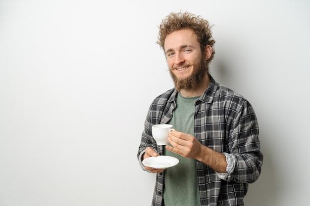 Улыбающийся красавец с вьющимися волосами и бородой пьет кофе и держит чашку
