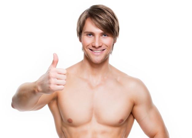 筋肉質の胴体で笑顔のハンサムな男は、親指を立てるサインを示しています-白い壁に隔離されています。