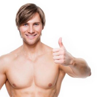 Smiling handsome man with muscular torso shows thumbs up sign - isolated on white wall.