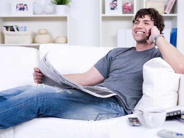 電話と新聞を持つハンサムな男の笑みを浮かべて-自宅で横になっています。