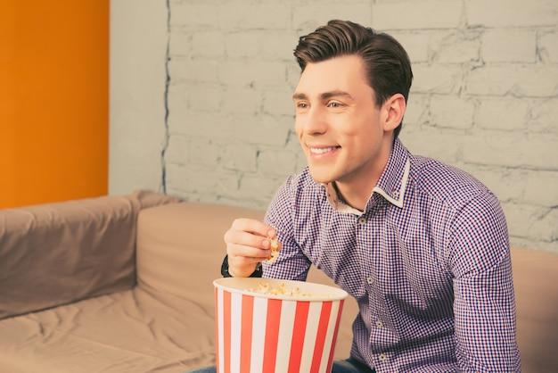 面白い映画を見ているポップコーンと笑顔のハンサムな男