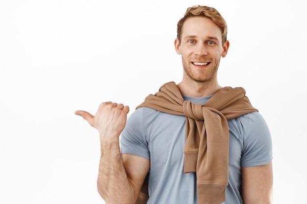 赤い髪のハンサムな男の笑顔、左を向いて幸せそうに見える、アドバイスを与える、広告のロゴを表示する、リンクをクリックすることをお勧めします、白い壁の上に立っています