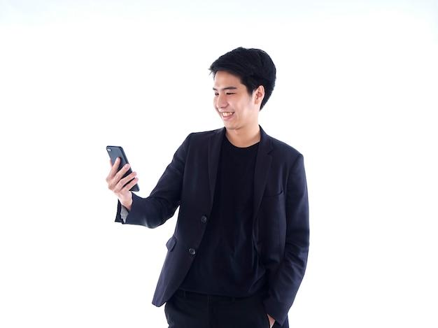 白の上に立っている間、ビデオ通話を持っているスマートフォンでハンサムな男の笑顔