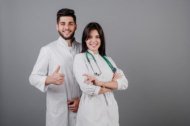 Smiling handsome medical doctors in robes smiling isolated over grey