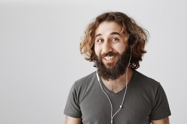 이어폰에 웃는 잘 생긴 중동 남자 듣는 음악