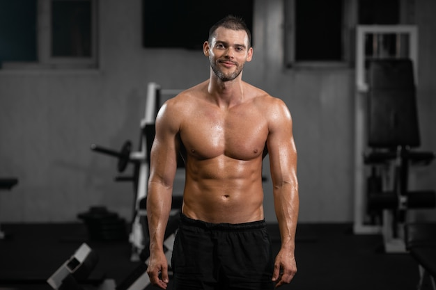 Smiling handsome muscular male athlete in gym