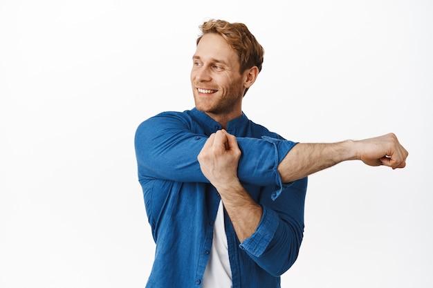 笑顔のハンサムな赤毛の男が手を伸ばして、コピースペースを左に見て、トレーニングの準備をして、白い壁の上に立って