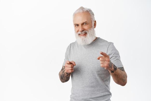 Sorridente bell'uomo anziano con tatuaggi che ti invitano, indicando la parte anteriore con un'espressione felice del viso, cercando persone, lodando il buon lavoro, in piedi sul muro bianco