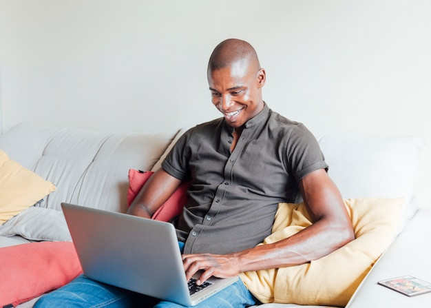 Smiling handsome shaved young man sitting on sofa using laptop