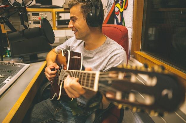 Улыбающаяся красивая певица, записывающая и играющая на гитаре