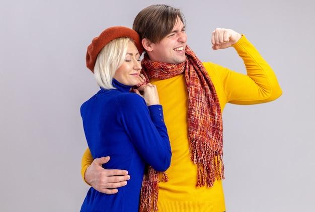 Sorridente bell'uomo slavo con sciarpa intorno al collo che abbraccia compiaciuta bella donna bionda con berretto e guardando il lato isolato sul muro bianco con spazio di copia