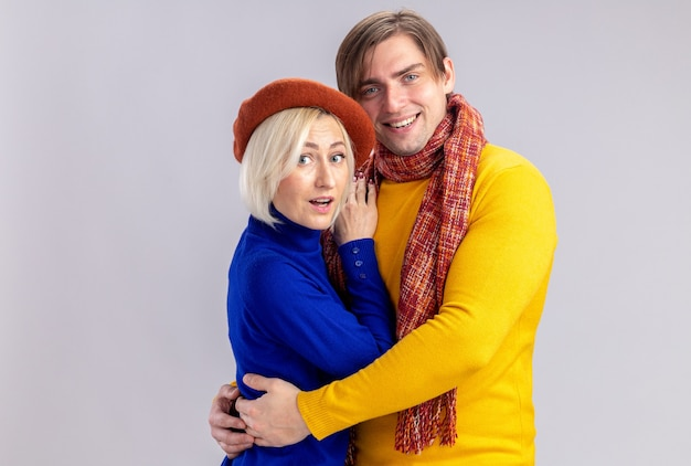 Smiling handsome slavic man with scarf around his neck hugging surprised pretty blonde woman with beret isolated on white wall with copy space