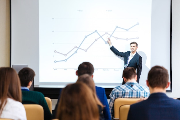 立っているハンサムなスピーカーの笑顔と会議場でのビジネス会議のグラフを説明します