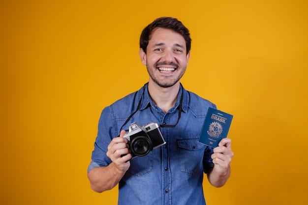 노란색 배경에 여권과 사진 카메라를 들고 웃는 잘 생긴 관광 남자.