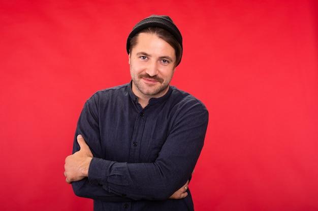 赤いスタジオで腕を組んでポーズをとっているニット帽のハンサムな無精ひげを生やした男に笑う