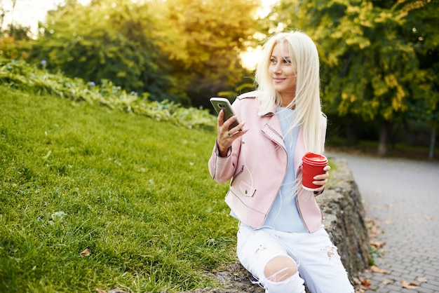 Smiling handsome woman listening relaxing music in the headphones with her mobile phone or tablet at the park. student listens to an online lecture and prepares for exams.